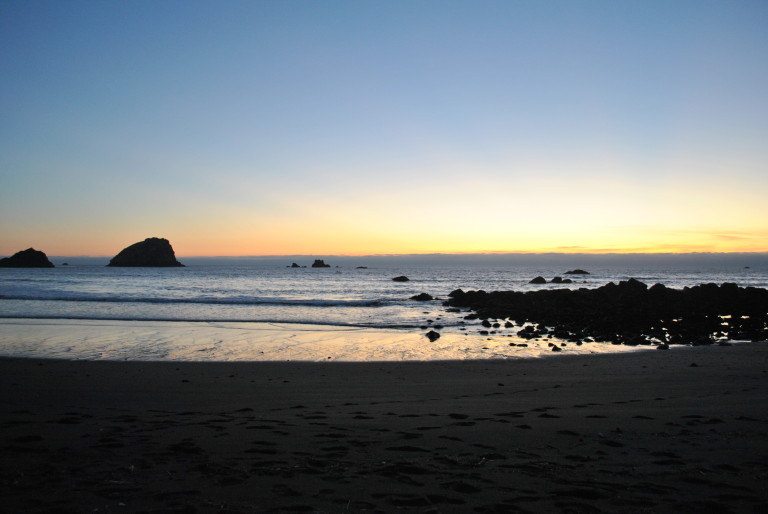 The sun sets over a black sand beach near Crescent City, Calif., in October of 2014.